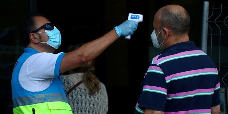 A un hombre le controlan la temperatura antes de una prueba de antígeno de la enfermedad por coronavirus (COVID-19) en Madrid/ REUTERS