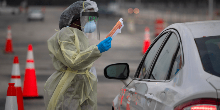 Un trabajador de la salud sostiene un folleto informativo sobre la enfermedad por coronavirus (COVID-19) para un residente en un lugar de pruebas de autoservicio en Houston