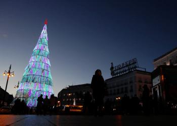 La gente se reúne alrededor de un árbol de Navidad en la plaza Puerta del Sol de Madrid