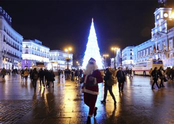 Una artista callejera vestida como Santa Claus camina en la Puerta del Sol en Madrid.(femenino)