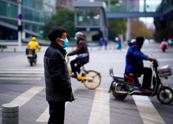 Hombre con una máscara parado cerca de una calle, casi un año después del inicio del brote de la enfermedad por coronavirus (COVID-19), en Wuhan, Hubei