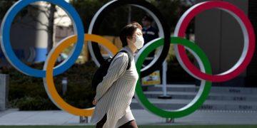 Las personas con máscaras faciales protectoras, después de un brote del coronavirus, se ven frente a los anillos olímpicos gigantes en la zona costera del Parque Marino Odaiba en Tokio, Japón, el 27 de febrero de 2020. © Athit Perawongmetha / Reuters