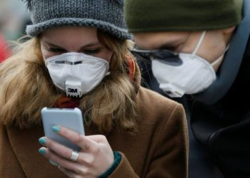 Imagen de archivo referencial de gente utilizando mascarillas mientras usan sus teléfonos inteligentes en una calle durante el brote de COVID-19, la enfermedad que causa el coronavirus, en Kiev, Ucrania. 17 de marzo, 2020. REUTERS/Valentyn Ogirenko/Archivo