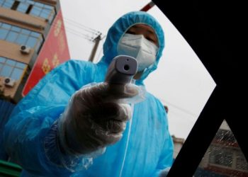 Sanitario tomando la temperatura con un termómetro infrarrojo Thomas Peter Thomson | Reuters
