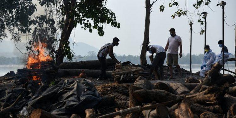 Trabajadores municipales incineran a víctimas de la covid-19 en Guwahati, India, el 25 de abril de 2021 | Shutterstock / Talukdar David