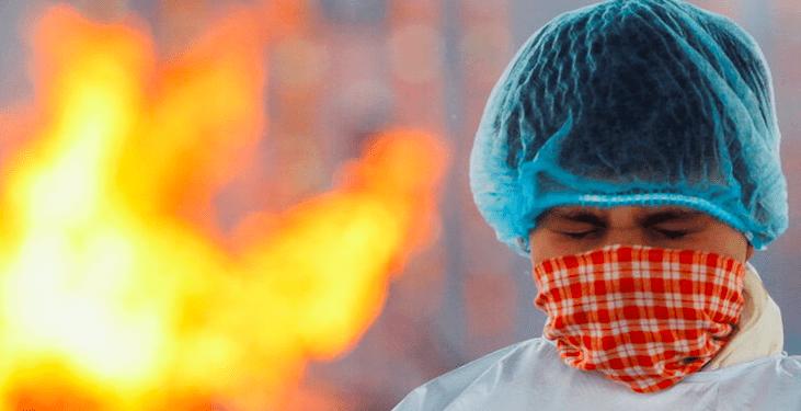 Un trabajador en un crematorio de cadáveres en la India durante la pandemia de la COVID-19. Reuters